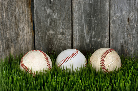 hardball: Three baseballs on green grass with room for your type.