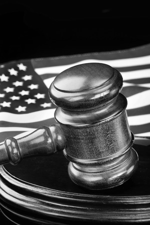 attorney: Wooden gavel and American flag with room for your type in black and white,