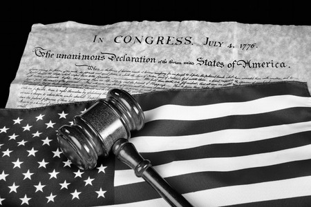 declaration: Declaration of Independence with American flag and wooden gavel in black and white.