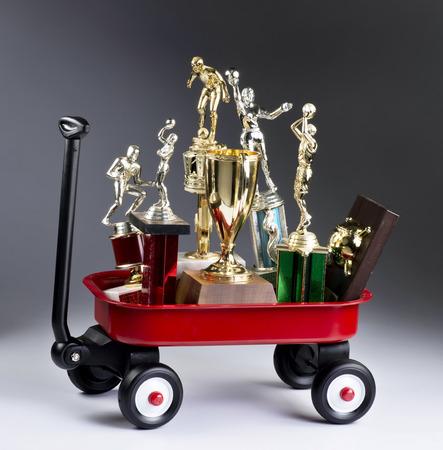 Little red wagon full of sports trophys.