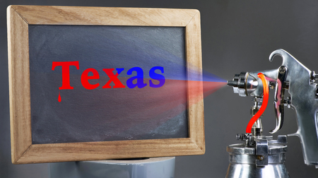 Air spray painting Texas blackboard sign.