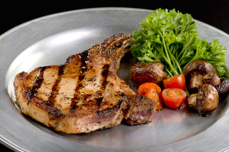 Grilled fresh pork chop with mushrooms and cherry tomatoes.