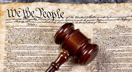 Wooden gavel on top of American Bill of Rights document, We the People. Stock Photo