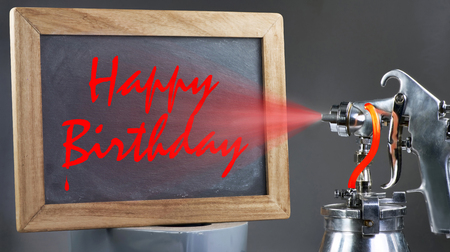 Spray painting happy birthday on blackboard.