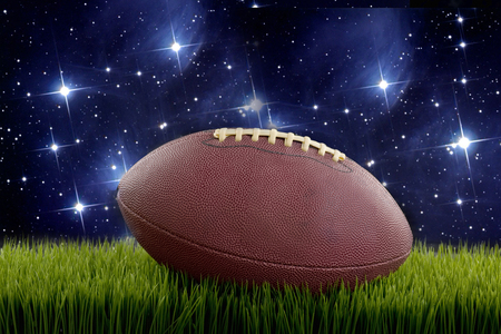 Football on green turf and stars in sky.