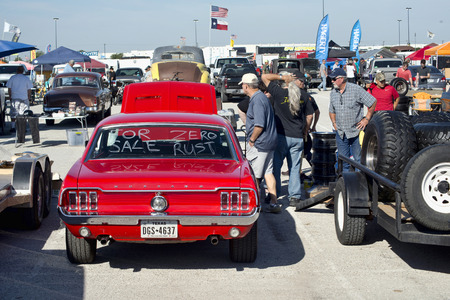 Grand Prairie, Texas- Oct.29,2016  Cars for sale at  local car swap meet. people looking at a 1966 red Ford Mustang. Editorial