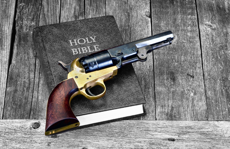 Old Western pistol on Holy Bible with room for your type. Stock Photo