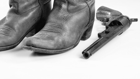 peacemaker: Old cowboy boots and  cowboy pistol in black and white with room for your type..