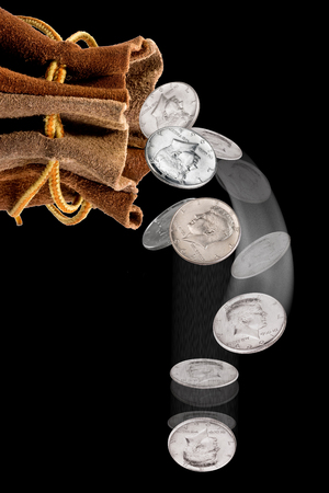 Bag of silver half dollars falling out of money bag. Stock Photo