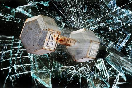 Dumbbell weight through broken glass window.
