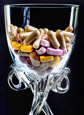 Pills and drugs in a wine glass. Stock Photo