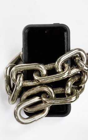 Cellphone locked up in brass chain in black and white.