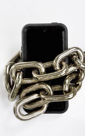 Mobiele telefoon geblokkeerd in koper ketting in zwart-wit. Stockfoto