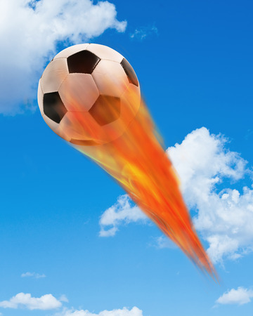 Soccer ball on fire and flying fast in the sky. Stock Photo