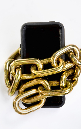 Cellphone locked up in brass chain. Stock Photo