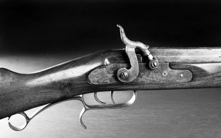 peacemaker: Old black powder cap and ball double trigger rifle in black and white.