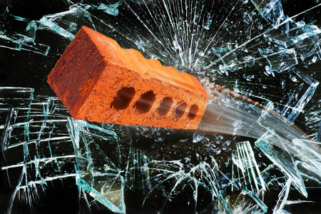 Flying brick through broken glass window. Stock Photo