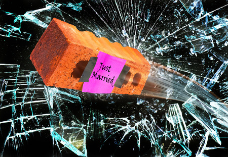 Just married with orange brick flying through glass window.