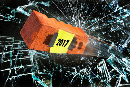 2017 year is like a brick flying through a broken window. Stock Photo