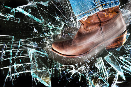 Western cowboy boots kicking and stomping shattered glass. Stock Photo