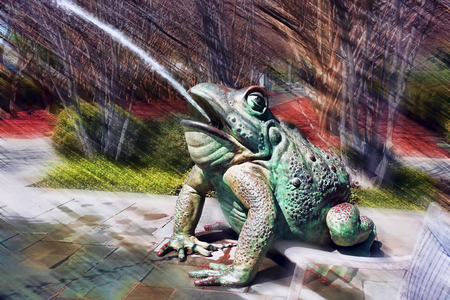 webbed: Surreal spitting green frog in park.
