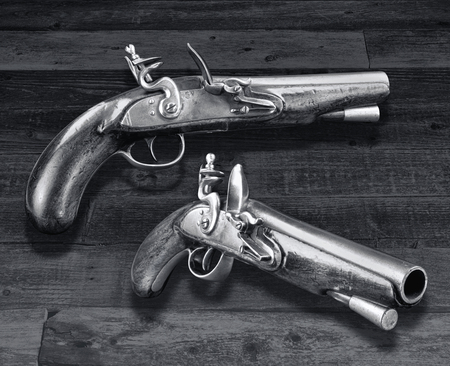 Antique English flintlock pistols made in the late 1700s in black and white.