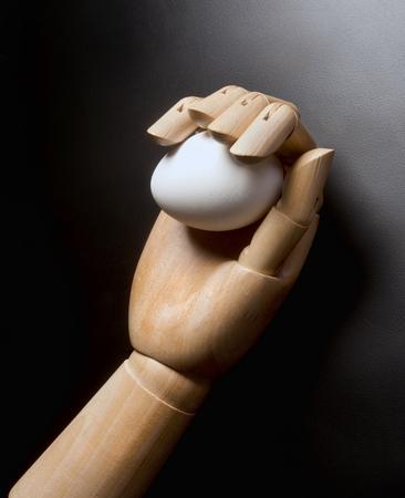 unbroken: Egg in wooden hand Stock Photo