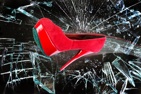 Red stiletto shoe through glass window.