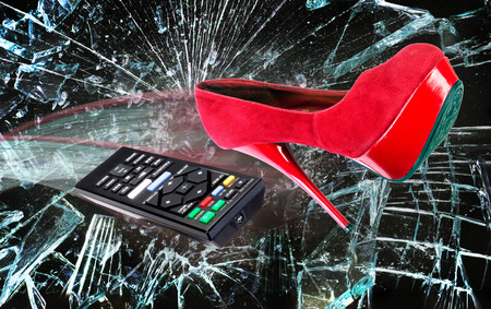 Red high heel shoe and remote control through broken glass.