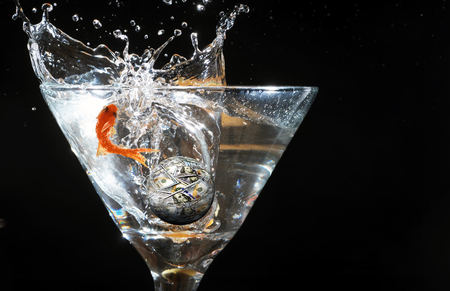 Gold fish jumping in martini glass with moneyball and room for your type. Stock Photo
