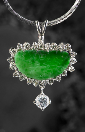highend: Antique green jade pendant and diamonds in white gold. Stock Photo