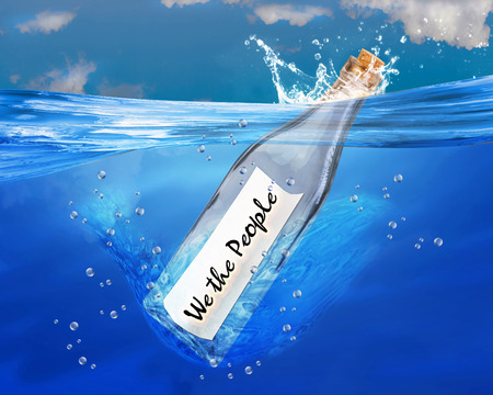 We the people in a message bottle floating in water. Stock Photo