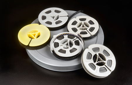 filmmaker: Old time 8mm film and film canisters. Stock Photo
