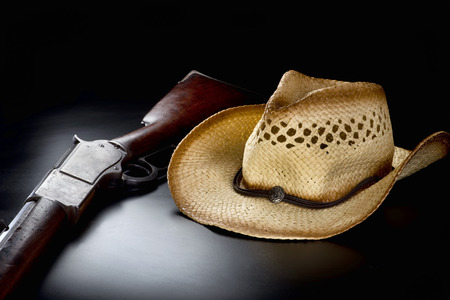 resistol: Viejo sombrero de paja de vaquero y rifle de acción de la palanca.