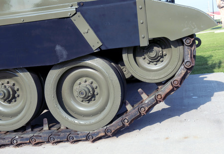 Closeup of an old army tank track and wheels.