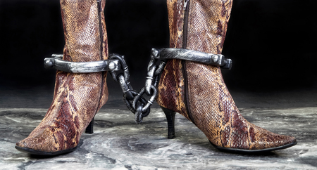 Snake skin boots in leg irons. Stock Photo