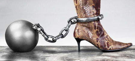 Lady in snakeskin boots locked with ball and chain.