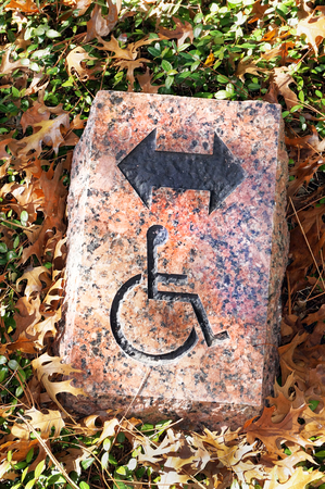 Handicapped direction sign on stone brick.