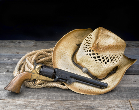 Cowboy pistol, straw hat and rope with room for your type. Reklamní fotografie - 91362228