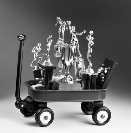Little red wagon full of sports trophys in black and white.