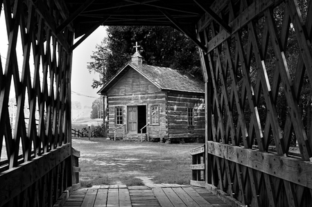 Old wooden log church view from wooden bridge in black and white.. Stock Photo