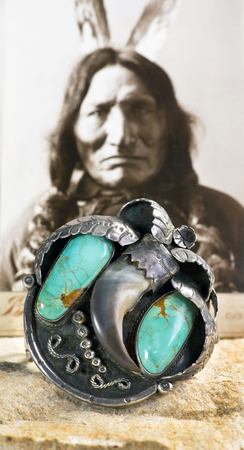 Dallas,Texas 1-15-18  Antique Navajo silver and turquoise bear claw cuff with old Indian warrior in background.. Stock Photo