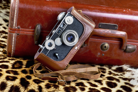Old style film camera against old suitcase ready for a safari vacation.