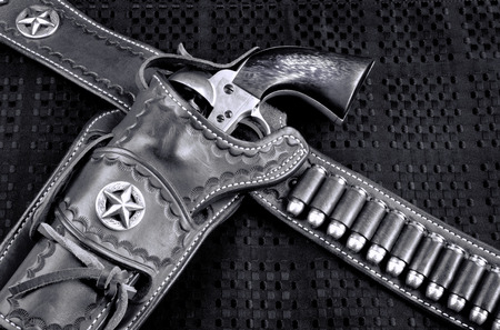 Old cowboy 45 pistol and leather tooled holster in black and white.. Stock Photo
