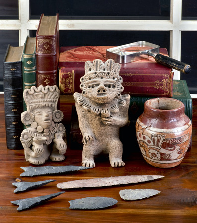 Antique Pre Columbian colection on table with old books.