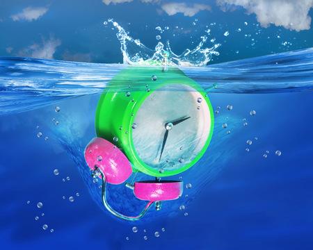 Alarm clock sinking in deep blue water.