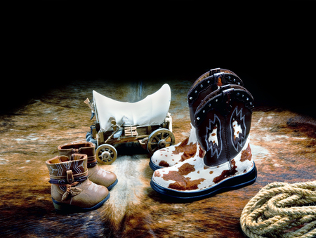 Cowboy boots,rope and western covered wagon with room for your type.