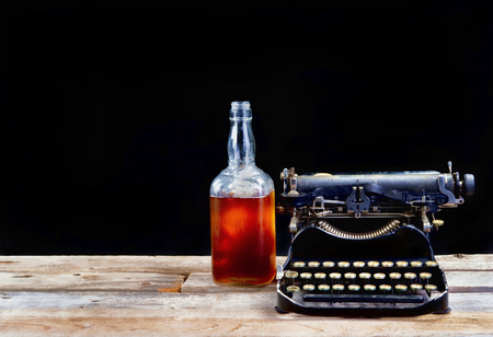 Antique portable typewritter made in 1917 with whisky bottle and room for your type . Stock Photo
