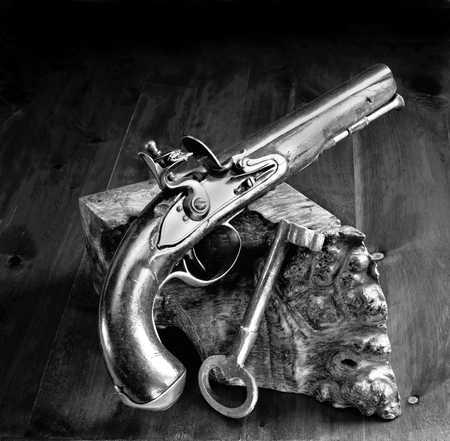 English flintlock pistol and jailers key made in the early 1800s in black and white.