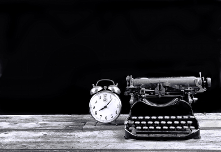 Antique portable typewritter and alarm clock made in 1917 with room for your type in black and white. 版權商用圖片 - 114901206
